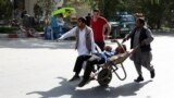 AFGHANISTAN -- Afghan men carries a wounded man after the second blast in Kabul, Afghanistan, Monday, April 30, 2018