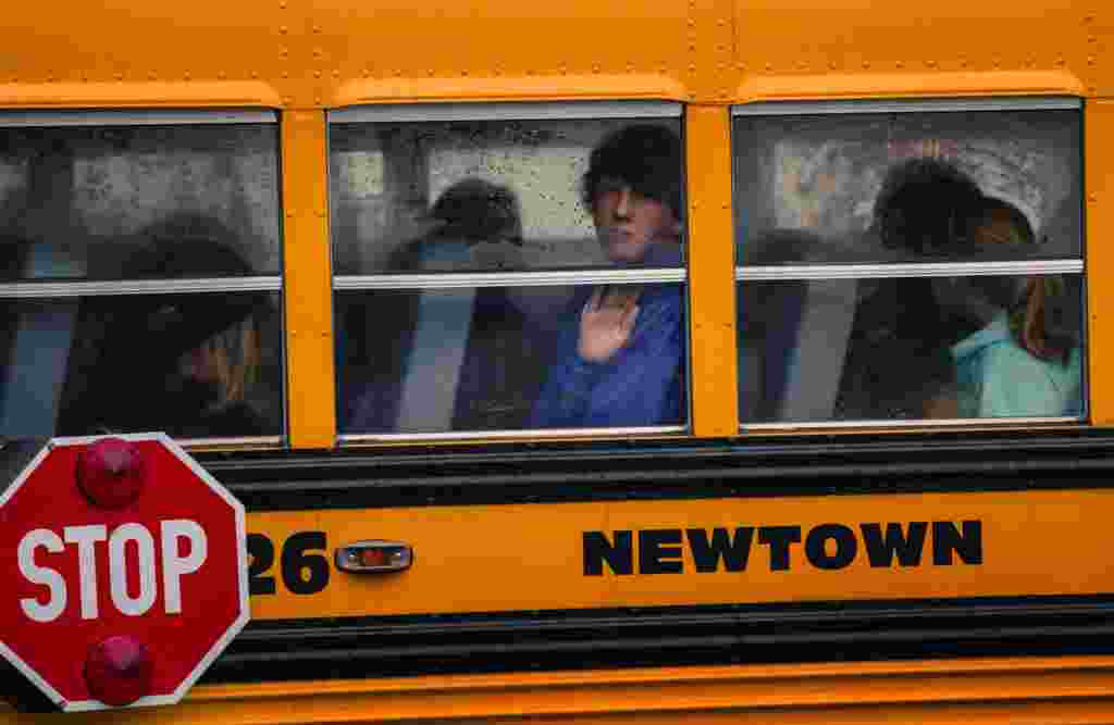 Children look out the windows of a school bus as it pulls into Newtown High School in Newtown, Connecticut. Students returned to school in the shattered Connecticut town on December 18, accompanied by police and counselors to help them cope with grief and fear after a shooting rampage that killed 26 people in the town, 20 of them small children. (Reuters/Lucas Jackson)