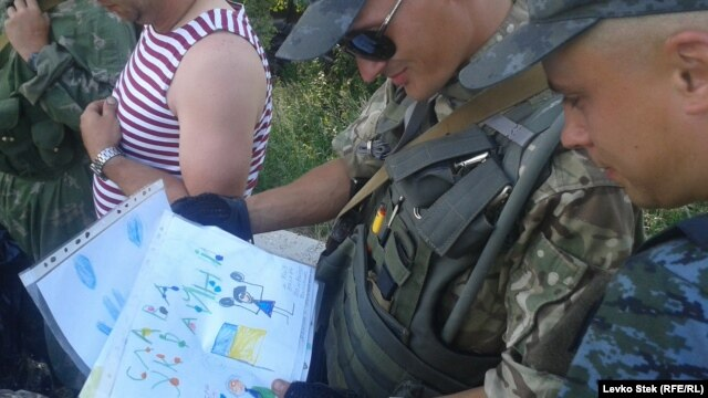 Soldiers enjoy the children's drawings they've received.