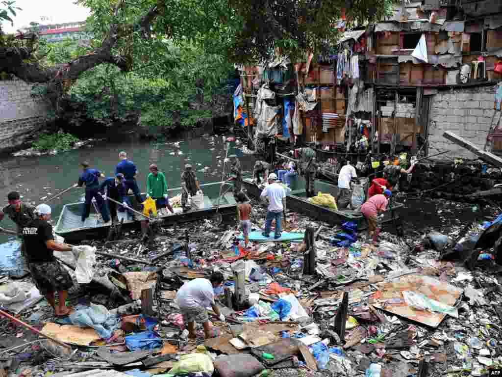 "U.S. sailors from the visiting aircraft carrier ""USS George Washington,"" in blue coveralls, join their Filipino counterparts in cleaning a heavily polluted waterway in a Muslim area of Manila on September 6. The carrier is in Manila for a four-day goodwill visit to carry out humanitarian projects. Photo by Jay Directo for AFP"