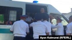 Полицейские заталкивают задержанного рядом с площадью человека в служебный микроавтобус. Алматы, 6 июля 2018 года.