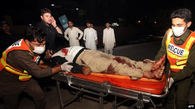 Volunteers move an injured policeman to a hospital following a bomb explosion in Peshawar on July 18.