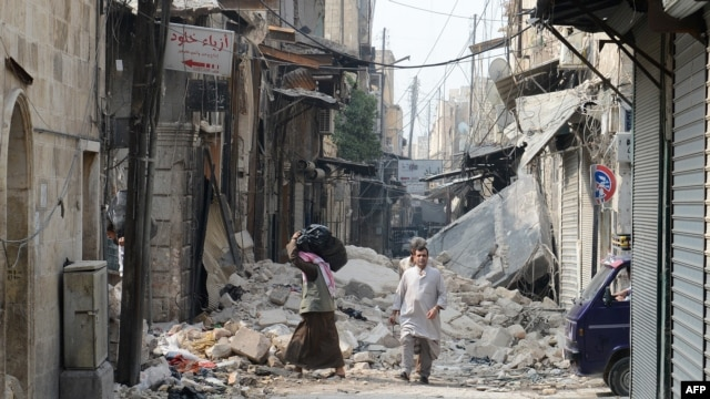 Syria -- Civilians walk past debris from destroyed buildings in the old sector of the northern city of Aleppo, 23Oct2012