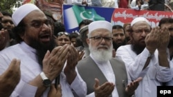 Hafiz Saeed, left, head of the banned Islamic charity Jamat-ud-Dawa, prays during a rally to mark Black Day, in Lahore, Pakistan, on July 19, 2016.