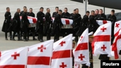 An honor guard carries the coffins of Georgian soldiers killed in Afghanistan at the airport in Tbilisi on May 16.