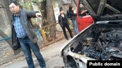 Гражданский активист Ермек Нарымбаев показывает свой сгоревший автомобиль. Алматы, 24 октября 2013 года.