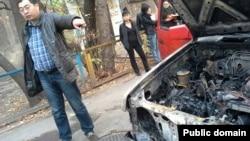 Гражданский активист Ермек Нарымбаев показывает на свою сгоревшую машину. Алматы, 24 октября 2013 года.
