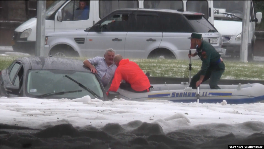 "A man is pulled from his vehicle by rescuers in an inflatable dinghy in video published by Shant News.   Grigorian says she saw four cars underwater near her house. But she says ""rescuers and an ambulance arrived very quickly."""