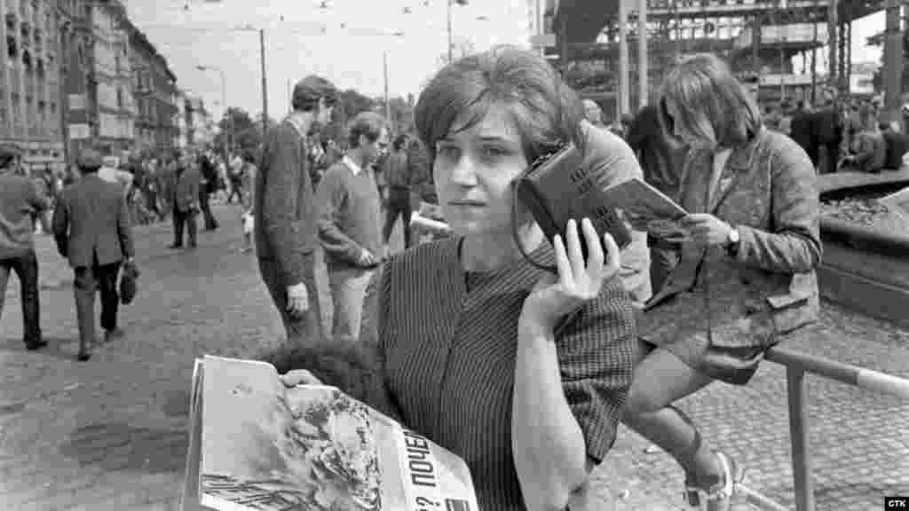 Женщина слушает последние новости. Радио во время вторжения играло важную роль. Чехословацкое радио передавало новости до того момента, пока помещение не заняли войска. Это произошло после серьезного столкновения у здания радио, где 17 молодых людей повредили танковые баки с бензином и подожгли его. Они надеялись, что это поможет задержать военных