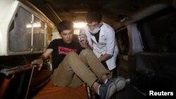 Медик помогает выбравшемуся из здания университета студенту.