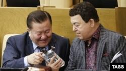 Йосип Кобзон (п) хвалиться колезі-депутатові пляшкою горілки «Кобзон» під час сесійного засідання Держдуми, 11 грудня 2014 року