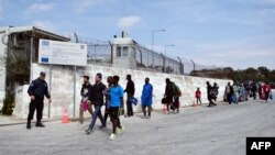 Архива - Грчки полицаец стои покрај мигранти во кампот Мориа на Лезбос.