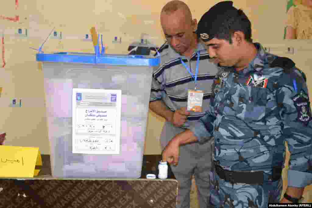 Policemen cast their votes during local elections in Basra.