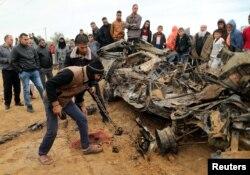 Палестинцы осматривают остатки автомобиля, уничтоженного авиаударом Израиля, сектор Газа, 12 ноября 2018 года