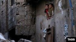 Илустрација - Сириски деца на прозорецот од нивната куќа во главниот град Дамаск, изрешетана од куршуми и шрапнели и излепена со политички постери со ликот на претседателот Асад