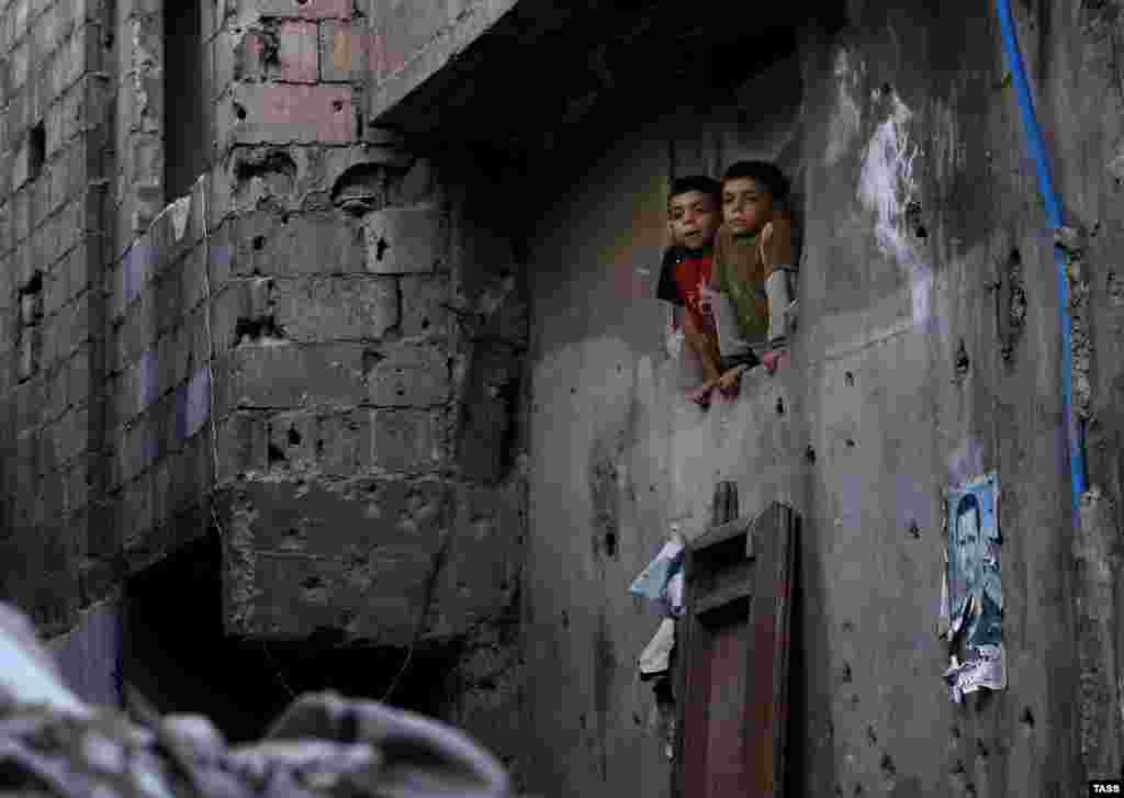 Children look out from the window of a residential building in the Syrian capital, Damascus. (TASS/Valery Sharifulin)