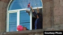 A woman celebrates the resignation of Armenian Prime Minister Serzh Sarkisian by banging on a cooking pot at her home in Yerevan on April 23.