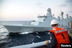 """Офицер норвежских ВМС с борта своего фрегата """"Хельге Ингстад"""" смотрит на сторожевой корабль ВМС Дании """"Эсберн Снаре"""". Оба корабля охраняют судно с сирийским химическим оружием"""