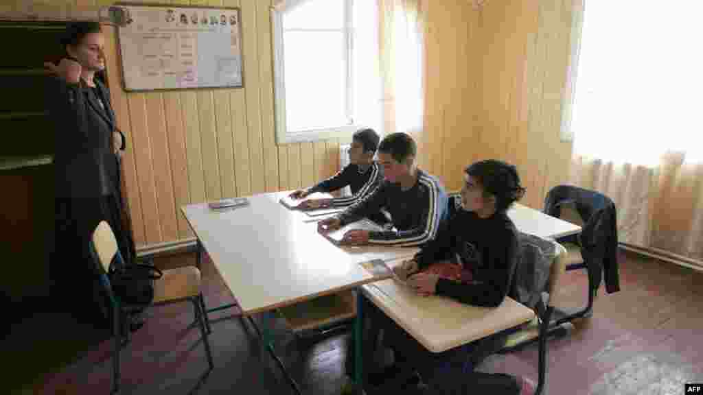A Georgian teacher gives a lesson for three schoolboys in the South Ossetian village of Akhmaji.
