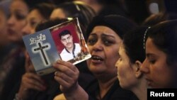 مسيحية مصرية تحمل صورة أحد ضحايا إشتباكات الأحد