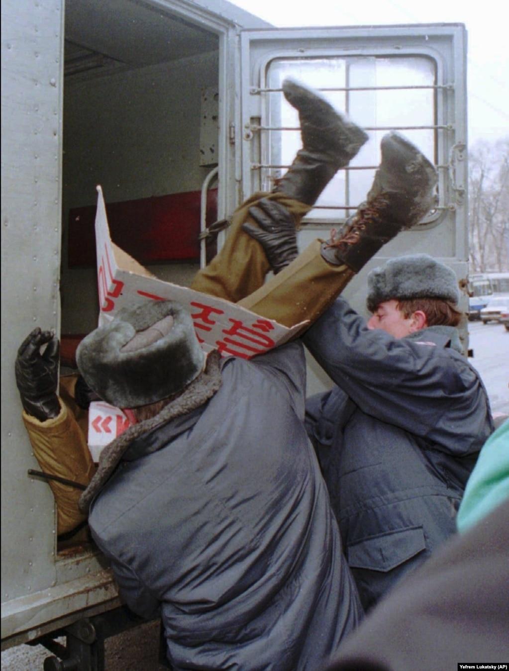 Милиция задерживает участника акции протеста в Киеве 12 января 1996 года. Несколько членов украинского парламента организовали протест против договора о безъядерном статусе Украины. В то время как силы охраны порядка загружают его в милицейский фургон, он держит плакат с требованием отставки министра обороны Украины Валерия Шмарова