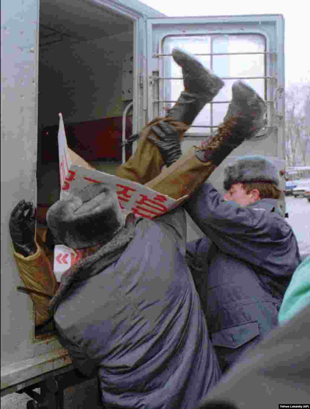 Police officers remove a protester from a rally in Kyiv on January 12, 1996. He was attending a demonstration organized by several members of Ukraine's parliament who were opposed to the denuclearization deal. As the protester is being thrown into a police van, he clings to a sign demanding the resignation of former Ukrainian Defense Minister Valeriy Shmarov.