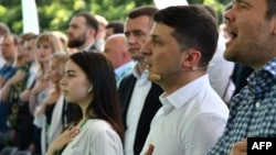 Ukrainian President Volodymyr Zelensky (second right) and participants sing the national anthem during his Servant of the People party's conference before the recent parliamentary elections. Many of the candidates chosen at this event will now be entering parliament for the first time.