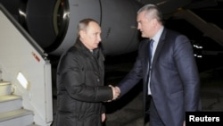 Russian President Vladimir Putin (left) shakes hands with Sergei Aksyonov, the de facto prime minister of the annexed Ukrainian peninsula, upon the former's arrival at Simferopol airport on December 2.