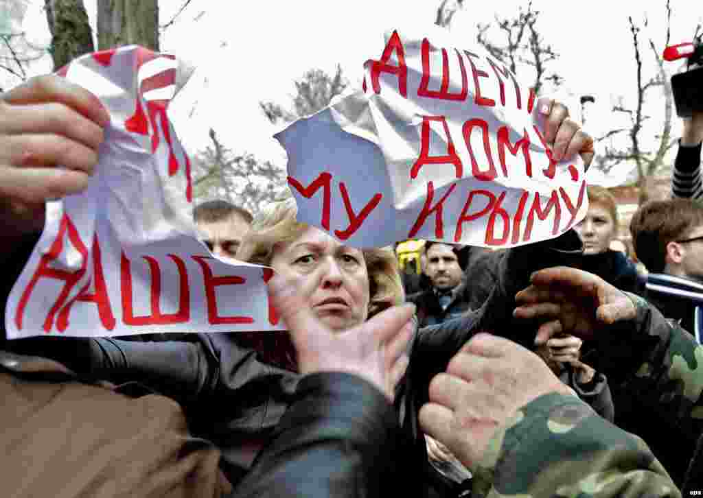 "Unidentified men tear apart a placard reading ""Peace for our home, our Crimea!'"" that a woman holds during a protest against war in Simferopol, Crimea, on March 5. (epa/Anastasia Vlasova)"