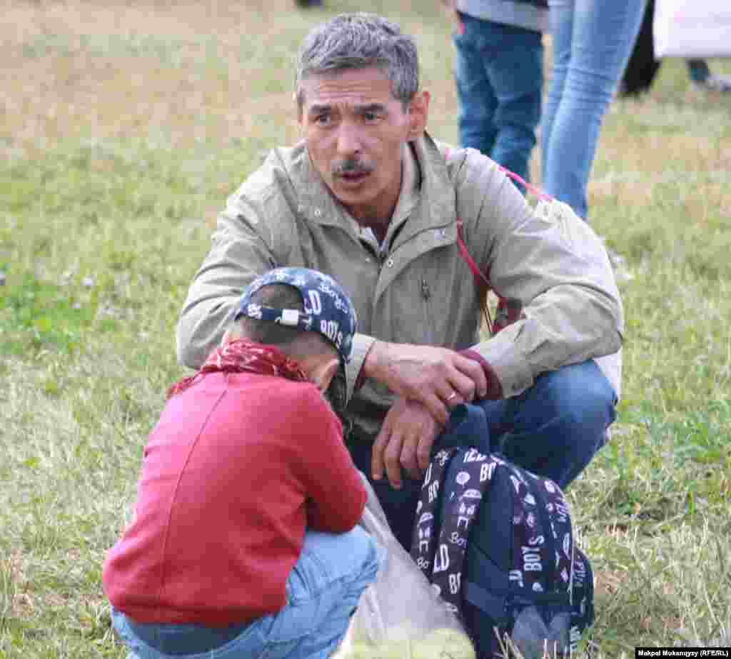 Отец с сыном отдыхают на лужайке.