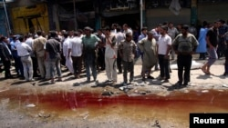 Residents stand next to a pool of blood and water after a car-bomb attack in Karbala on April 29.