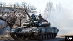 A Ukrainian tank drives on a road not far from the eastern Ukrainian city of Debaltseve on February 13, 2015.