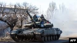A Ukrainian tank drives on a road not far from the eastern Ukrainian city of Debaltseve on February 13, 2015.