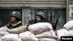 Syrian soldiers man a checkpoint in the city of Homs