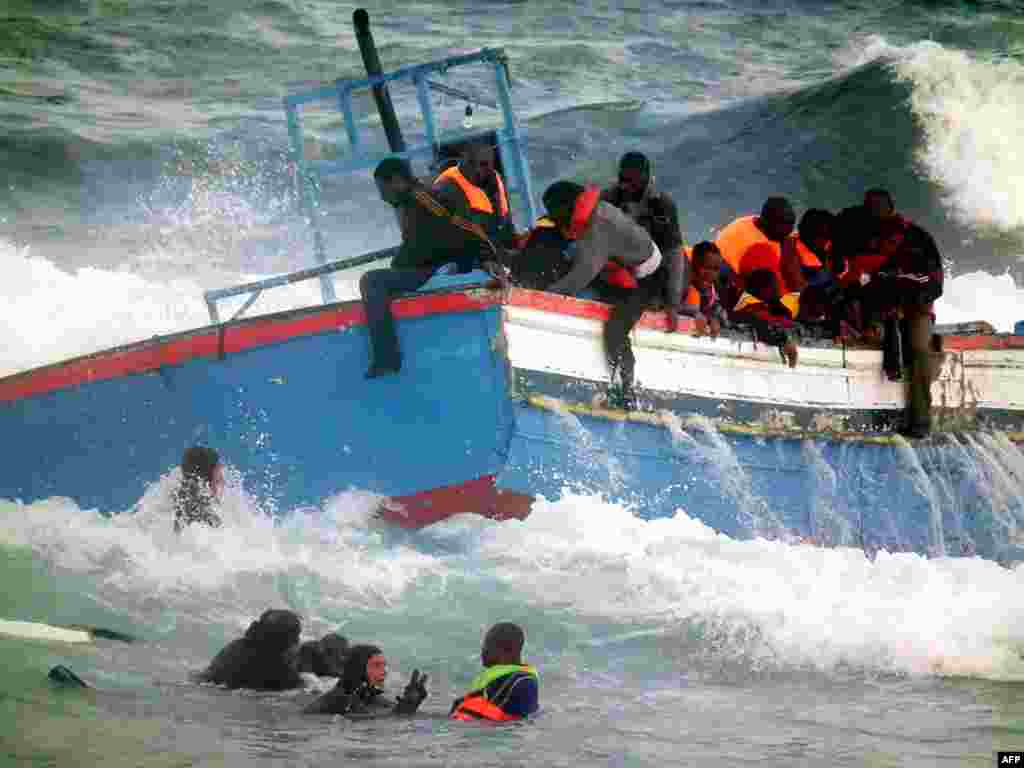 Rescuers help people in the sea after a boat carrying some 250 migrants crashed into rocks as they tried to enter the port of Pantelleria, an island off the southern coast of Italy, on April 13. A fishing boat that had sailed across the Mediterranean from Libya ran aground on rocks on Pantelleria, killing two women. Italy is struggling to cope with a mass influx of immigrants from North Africa, many of whom risk their lives by sailing across the often stormy Mediterranean in makeshift vessels. Photo by Francesco Malavolta for AFP