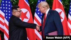 Президент США Дональд Трамп (справа) и лидер Северной Кореи Ким Чен Ын на встрече на острове Сентоса в Сингапуре. 12 июня 2018 года.