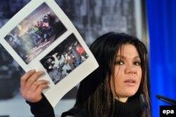Украинская певица Руслана держит фотографии украинских протестов на пресс-конференции в Берлине. 1 февраля 2014 года.