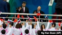 Президент Китая Си Цзиньпин (слева) и президент России Владимир Путин приветствуют зрителей на товарищеском матче между сборными Китая и России по хоккею с шайбой. Тяньцзинь, 8 июня 2018 года.