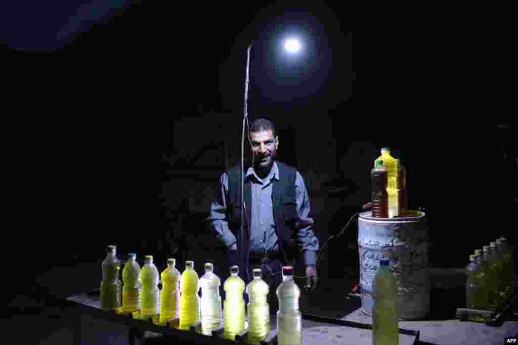A Syrian street vendor selling fuel uses a battery-powered lamp to light his stall at night in the rebel-held area of Douma, east of the capital Damascus, on April 27.