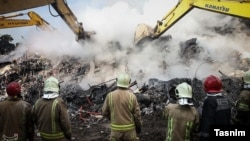 Rescue teams clear debris at the site of a high-rise building, which collapsed in Terhan on january 19.