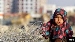 Афганская девочка-переселенка играет за пределами своего временного убежища для внутренне перемещенных лиц (ВПЛ) на окраине Кабула, Афганистан, 20 ноября 2015 года