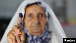 A woman shows her ink-stained finger after casting her vote during the National Assembly election in Benghazi.
