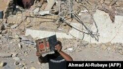 Чалавек трымае Каран, які знайшоў на руінах мячэці, зьнішчанай выбухам у Багдадзе 30 верасьня.