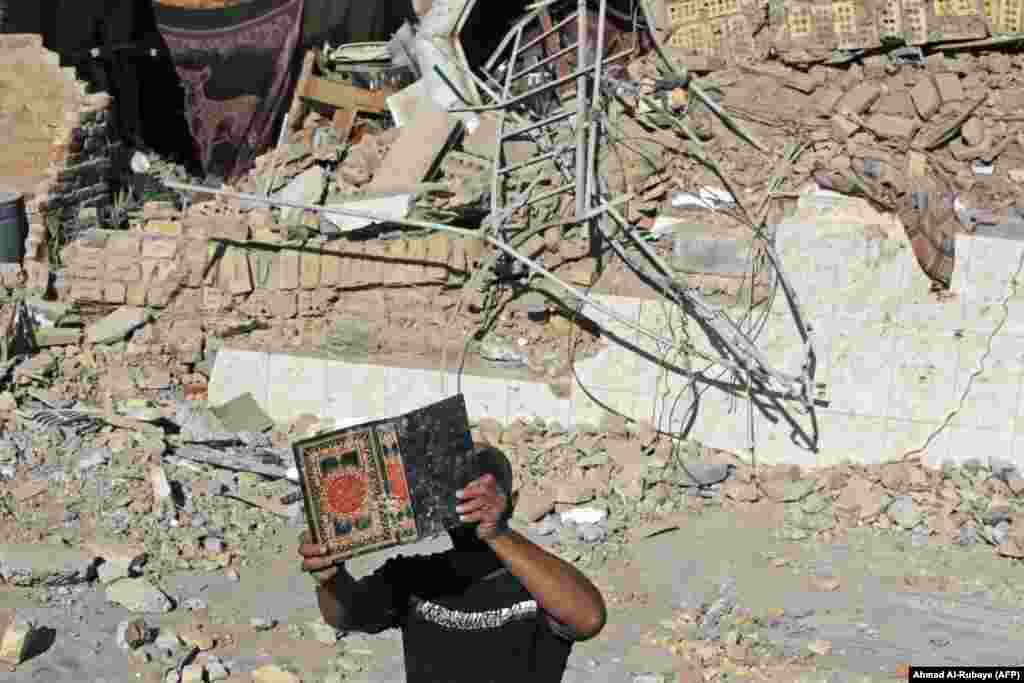 A man retrieves a copy of the Koran from the debris of Al-Hussein Mosque following an explosion in the district of Al-Musayyib, south of Baghdad. (AFP/Ahmad Al-Rubaye)