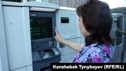 Банкоматтан ақша алып тұрған адам. Алматы, 21 маусым 2013 жыл. (Көрнекі сурет.)