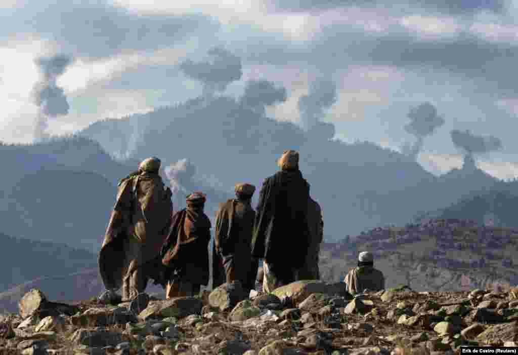 Афганские боевики наблюдают за взрывами американских бомб в горном комплексе Тора-Бора в Афганистане в декабре 2001 года. После того, как Соединенные Штаты вторглись в Афганистан после терактов 11 сентября, было проведено массированное воздушное нападение при поддержке наземных истребителей на серию горных пещер, известных как Тора-Бора. Считалось, что бойцы «Аль-Каиды» и самбин Ладен прятались в тех горах, прежде чем предводитель сбежал в Пакистан.