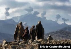 Афганские боевики, борющиеся против талибов, наблюдают за несколькими взрывами в результате бомбардировок США в горах Тора-Бора в Афганистане 16 декабря 2001 года