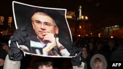 A demonstrator in Moscow holds a portrait of jailed tycoon Mikhail Khodorkovsky on December 31.
