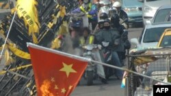 Наразылық танытушылар Қытайдың туын өртеп жатыр. Тайвань, 22 желтоқсан 2009 жыл. (Көрнекі сурет)