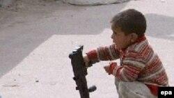 طفل عراقي وبندقية بلاستيكية